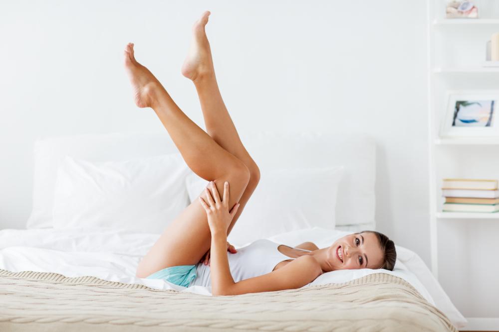 Mujer en una cama con las piernas en alto sin piel de naranja